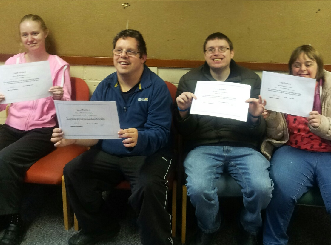 Group of four people holding up certificates